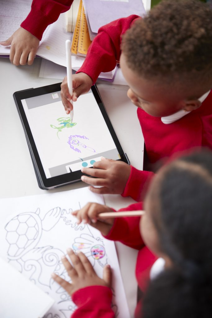 Ttwo kindergarten school kids in a classroom drawing with a tablet computer and stylus