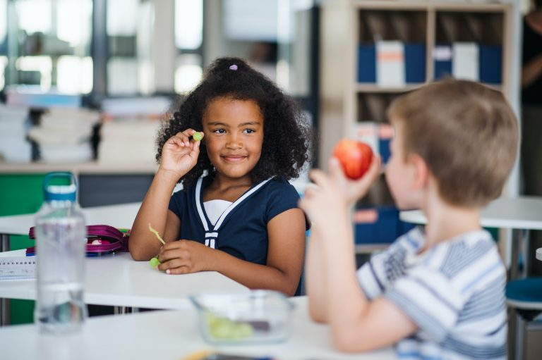 Small school children sitting at the desk in classroom, eating fruit